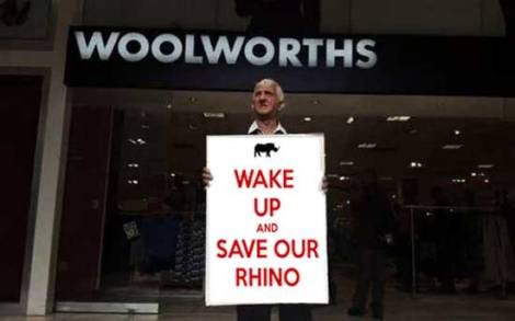 An angry protester demands that Woolworths save the rhino.
